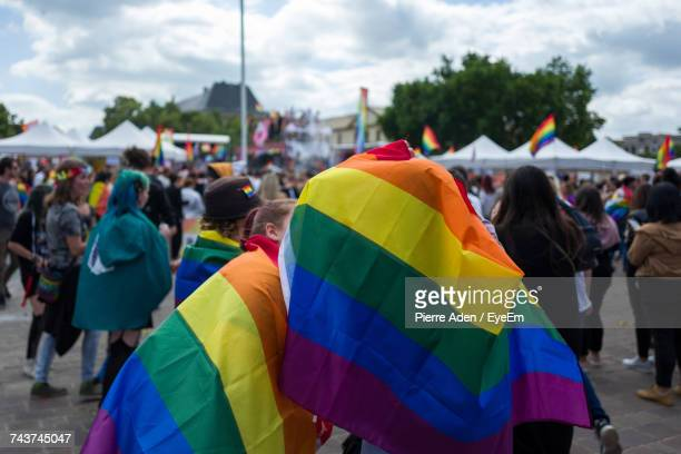 people covered with rainbow flags on street during gay pride parade - lorraine smothers stock pictures, royalty-free photos & images