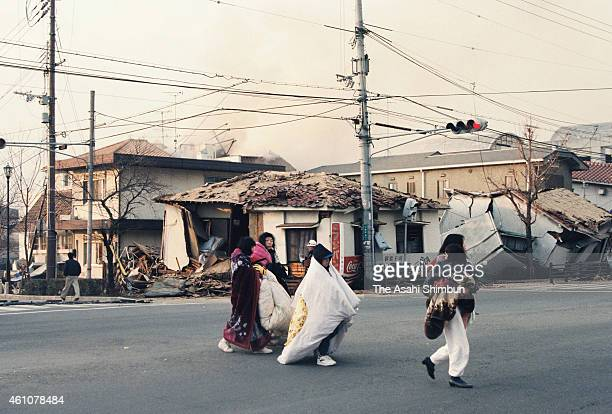 People covering themselves in blankets evacuate on January 17 1995 in Ashiya Hyogo Japan Magnitude 73 strong earthquake jolted in the morning of...