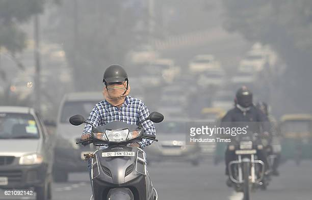 People covers himself with his handkerchief to avoid thick smog at ITO as city covered under a blanket of heavy smog air quality deteriorated sharply...