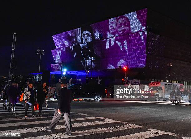 People cross 14th Street as images marking the ratification of the 13th Amendment passage of the Voting Rights Act and the end of the Civil War are...