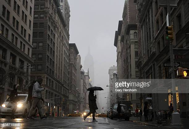 People cross 5th Avenue in the snow on January 14, 2017 in New York City.