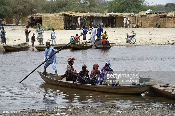 People cross a branch of Lake Chad on April 6 in N'Bougoua which was attacked by Islamist group Boko Haram on February 12 Seven civilians were killed...
