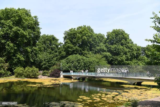 People cross a bridge in the hot weather in St James's Park in central London on June 21 2017 Europe sizzled under a continentwide heatwave on June...