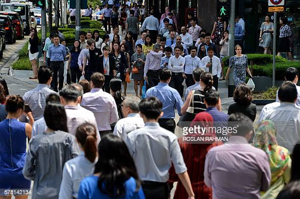 People cross a busy street during lunch break at the financial district in Singapore on July 21 2016 / AFP / ROSLAN RAHMAN