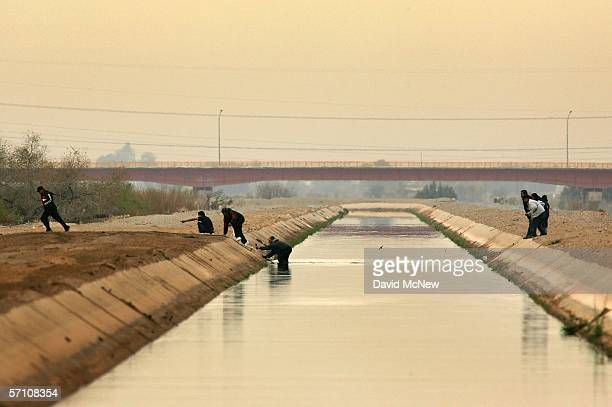 People cross a canal after walking over the dry Colorado River to cross illegally into the US from Mexico on March 16 2006 the border town of near...