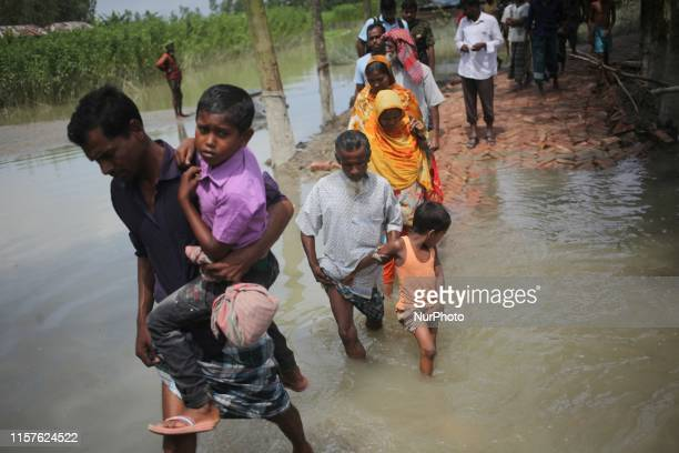 People cross a damaged Road as flood water reduced in Tangail, Bangladesh on 24 July 2019. At least 78 people have been killed and 120 are missing...