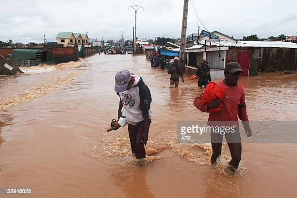 People cross a flooded road in the Sabotsy Namehana commune, north of Antananarivo on February 14, 2012 after Cyclone Giovanna hit Madagascar,...