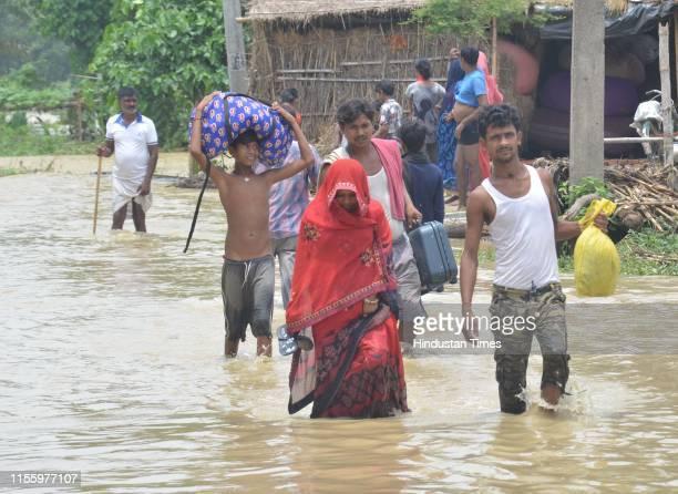 People cross a flooded street following incessant monsoon rainfall at Aurai Block on July 16 2019 in Muzaffarpur India Bihar is witnessing floods as...