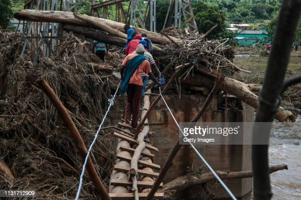 People cross a makeshift bridge over a river that surged days earlier during Cyclone Idai on March 20 2019 in Chipinge Zimbabwe Zimbabwean...