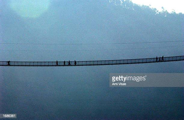 People cross a mountain range on a bridge December 13 2002 in Pokhara Nepal The country is suffering from a dramatic drop in tourism because of the...