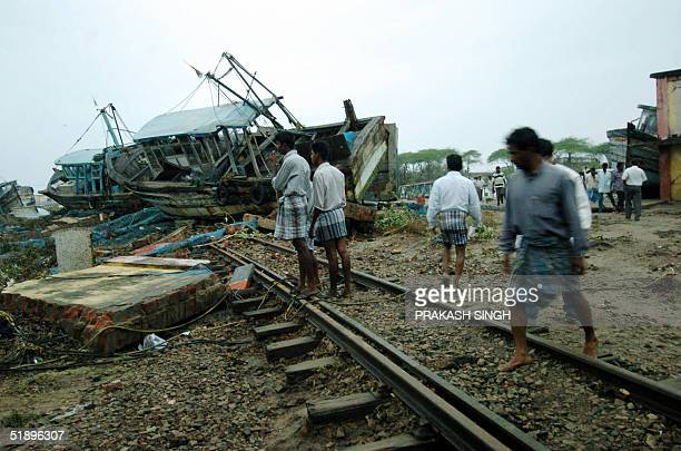 People cross a railway track with ships lying on it at Nagapattinam port some 350 kms south of Madras 27 December 2004 after tidal waves hit the...