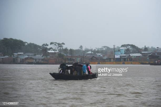TOPSHOT People cross a river on a boat ahead of the expected landfall of cyclone Amphan in Khulna on May 20 2020 India and Bangladesh began...