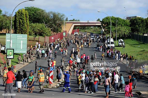 People cross a road after seeing the funeral cortege of South African former president Nelson Mandela leaving the Military Hospital on its way to the...