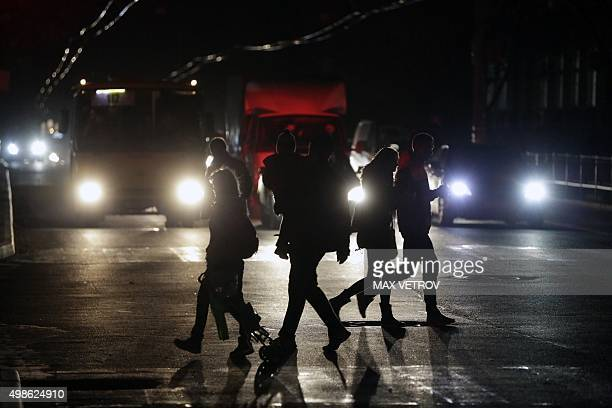 People cross a road during a power outage in the Crimean city of Simferopol on November 24 2015 Power cuts in Crimea affected nearly 940000 people on...