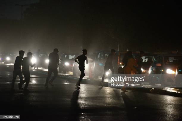 People cross a road during the dust storm at Barakhama Road on June 9 2018 in New Delhi India The dust storm pushed the temperature down by a few...