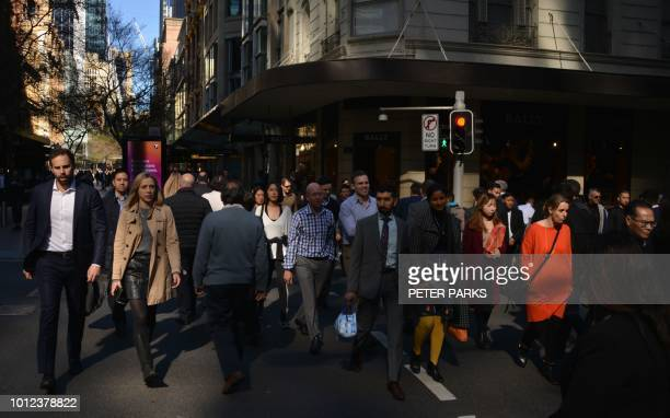 People cross a road in the central business district of Sydney on August 7 2018 Australia's population will reach the 25 million mark on August 7...