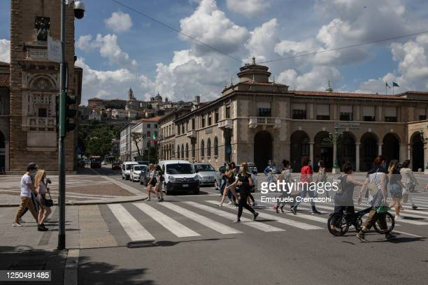 People cross a road in the Lower Town on June 18, 2020 in Bergamo, Italy. The city of Bergamo is slowly returning to normality after the lockdown for...