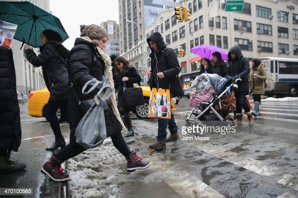 People cross a slushy Park Avenue on February 18 2014 in New York City The city has reportedly received a total of about four feet of snow so far in...