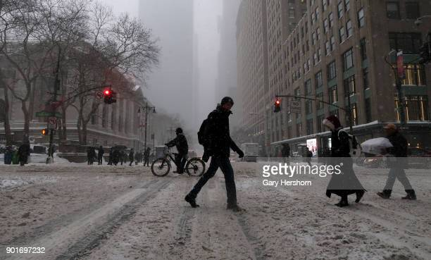 People cross a snow covered 42nd Street during a winter storm called a 'bomb cyclone' on January 4 2018 in New York City