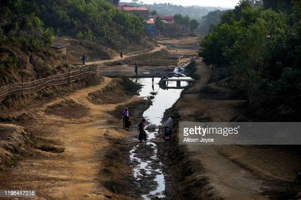 People cross a stream in a Rohingya refugee camp on January 23, 2020 in Cox's Bazar, Bangladesh. On Thursday, the International Court of Justice...