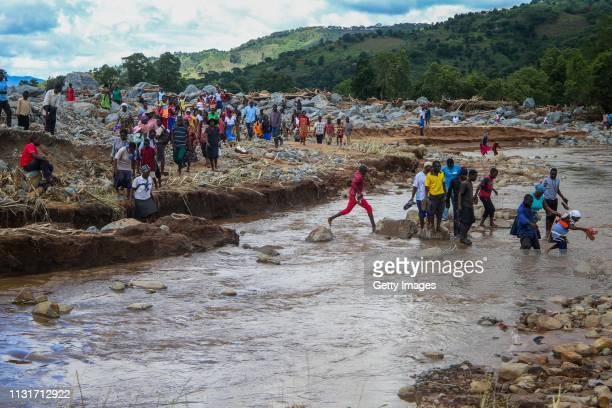 People cross a stream in an area flooded by Cyclone Idai on March 20 2019 in Chipinge Zimbabwe Zimbabwean authorities have said more than 100 people...