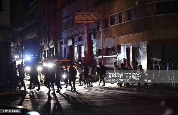 "People cross a street during a power cut in Caracas on March 7, 2019. - The government of Nicolas Maduro denounced a ""sabotage"" against the main..."