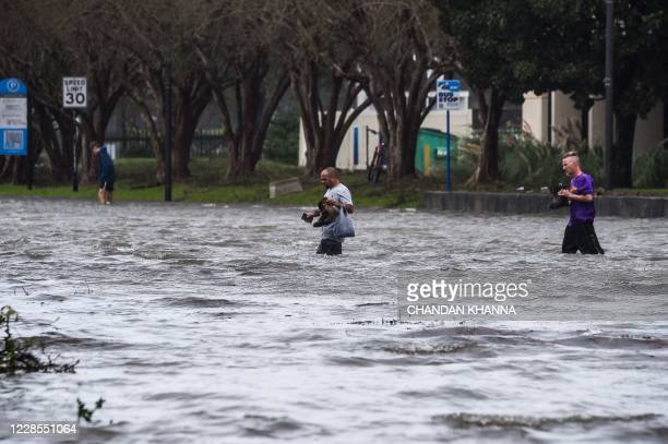 TOPSHOT People cross a street flooded by Hurricane Sally in Pensacola Florida on September 16 2020 Hurricane Sally barrelled into the US Gulf Coast...