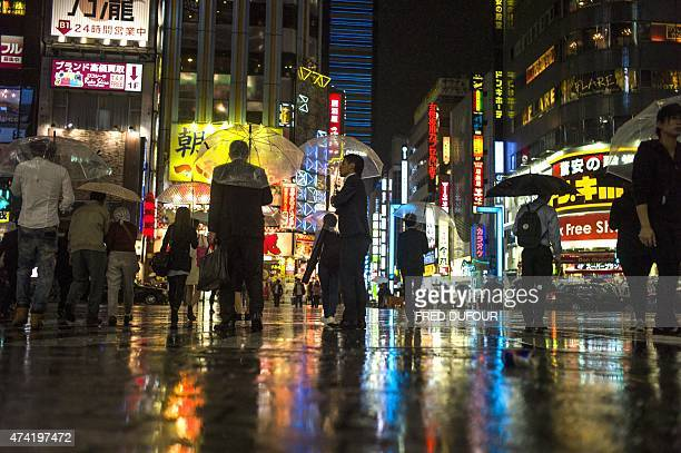 People cross a street in Shinjuku district in Tokyo on May 12 2015 AFP PHOTO / FRED DUFOUR
