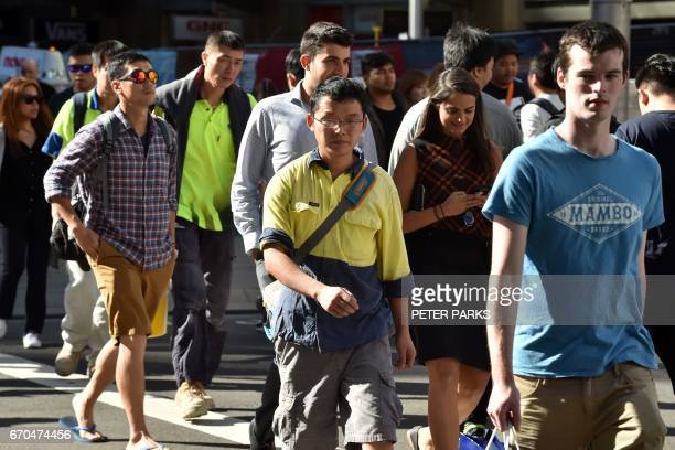 People cross a street in Sydney on April 20 2017 Canberra on April 20 unveiled plans to put 'Australian values' at the heart of tougher requirements...