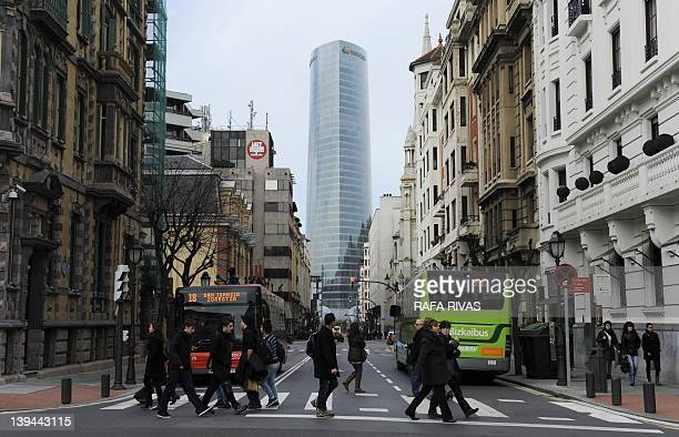 People cross a street near Iberdrola Tower on February 21 2012 in the Northern Spanish Basque city of Bilbao The Iberdrola Tower building was...