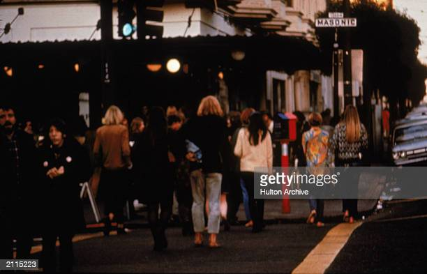 People cross an intersection in the Haight Ashbury nieghborhood of San Francisco California late 1960s