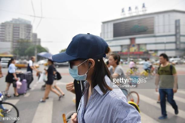 """People cross an intersection on a hazy day in Beijing on July 20, 2017. Chinese cities had fewer """"good air"""" days in the first half of 2017 compared..."""