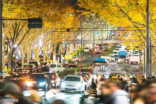 people cross and cars go through rows of illuminated autumn leaves trees omotesando street for winter holydays season in the duskt at jingumae, shibuya tokyo japan on december 06 2017. - 表参道 ストックフォトと画像