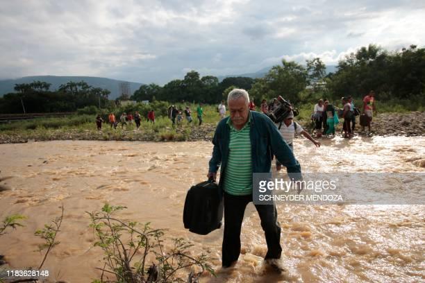 TOPSHOT People cross from San Antonio del Tachira in Venezuela to Cucuta in Colombia through trochas illegal trails near the Simon Bolivar...