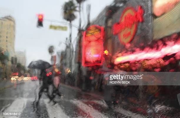 TOPSHOT People cross Hollywood Blvd as rain falls in Hollywood California January 14 2019 A storm over Southern California delivered rain and snow...