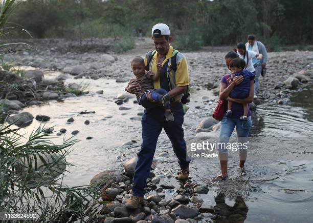 People cross into Venezuela through the low waters of the Táchira River near the Simón Bolívar international bridge on March 4 2019 in Cucuta...