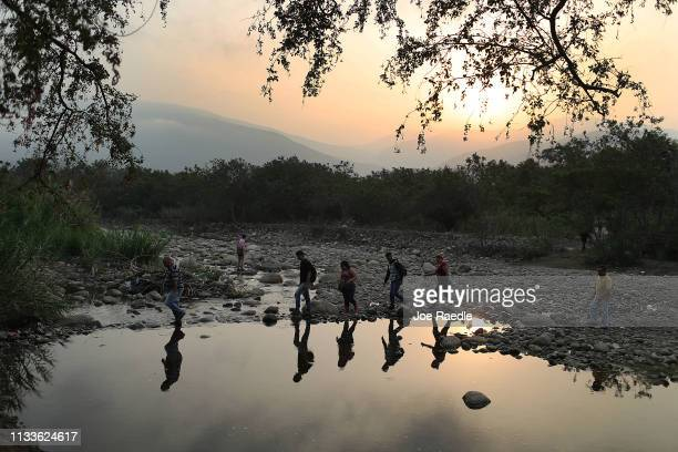 People cross into Venezuela through the low waters of the Táchira River near the Simón Bolívar international bridge on March 4 2019 in Cucuta...