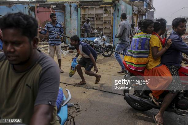 People cross near damaged electric wires after Cyclone Fani passed through Puri Odisha India on Saturday May 4 2019 A category 4 storm with strong...