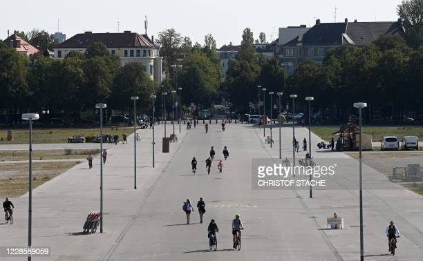 People cross over the empty Theresienwiese in Munich, southern Germany, the place of the yearly beer festival, on September 19, 2020. - The...