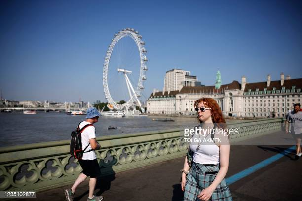 People cross over the River Thames as they walk along Westminster Bridge, backdropped by the landmark the the London Eye, in London on September 7,...