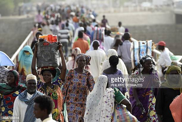 People cross the border between Chad and Cameroon on the N'Gueli bridge on April 4 2015 near Djamena N'Gueli bridge is a major border crossing for...