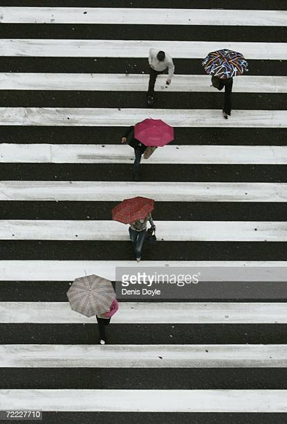 People cross the Gran Via road as rain lashes down on October 20 2006 in Madrid Spain