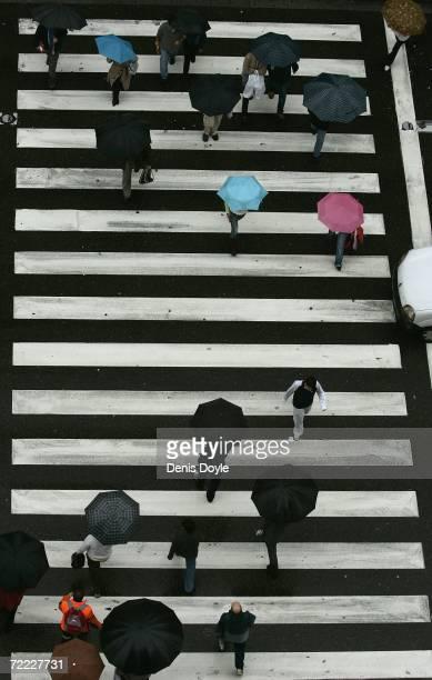 People cross the Gran Via road as rain lashes down on October 20 2006 in Madrid Spain
