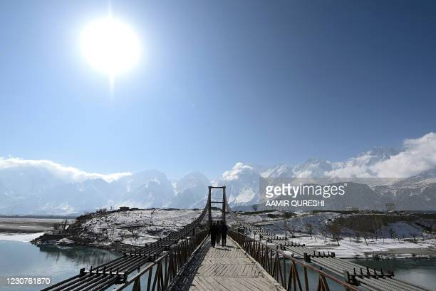 People cross the Kowardu suspension bridge over the Indus River on the outskirts of Skardu on January 24, 2021.