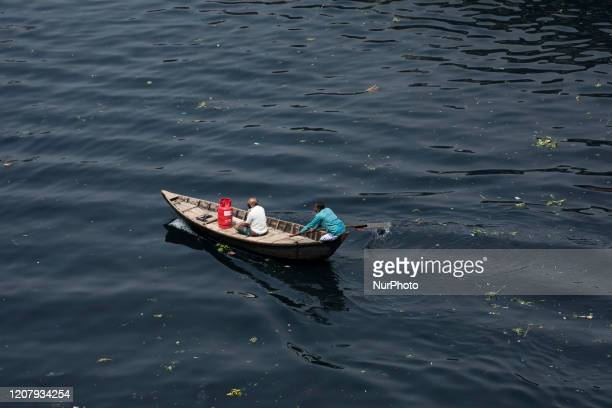 People cross the polluted Buriganga river by boat in Dhaka Bangladesh on March 21 2020 The chemical waste of mills and factories household waste...