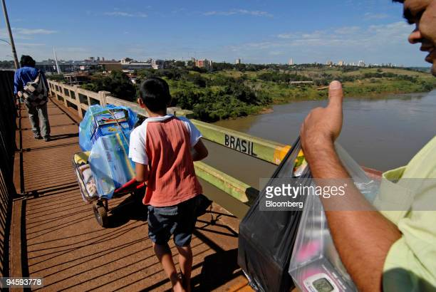 People cross the Ponte da Amizade Friendship Bridge with imported goods from Paraguay to Brazil in Foz do Iguacu Brazil on May 10 2007 In a parking...