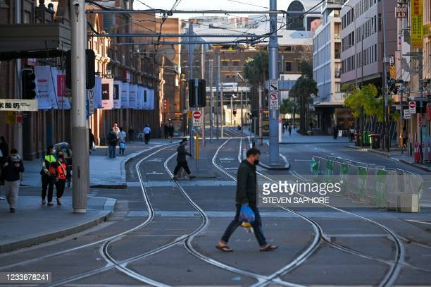 People cross the road in an empty section of Chinatown in Sydney on June 27 on the first full day of a two-week Covid-19 coronavirus lockdown to...