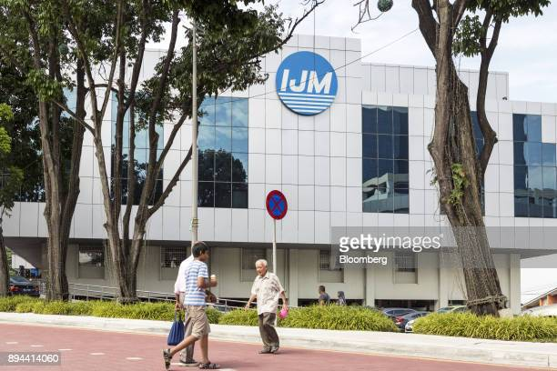People cross the road in front of the IJM Corp offices in Kuala Lumpur Malaysia on Tuesday May 30 2017 IJM is Malaysia's biggest builder by revenue...