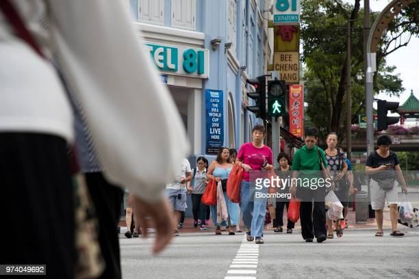 People cross the road in the Chinatown area of Singapore on Wednesday June 13 2018 Tourism as well as the consumer sector will likely see a lift...