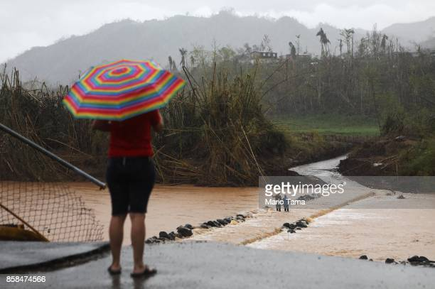 People cross the San Lorenzo de Morovis river as a woman watches from the edge of a destroyed bridge more than two weeks after Hurricane Maria hit...